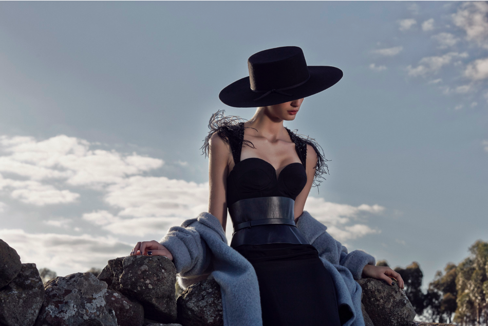 Girl sitting on a rock with the late grey and cloudy sky behind looking down dressed in a black dress and a very wide black leather belt.