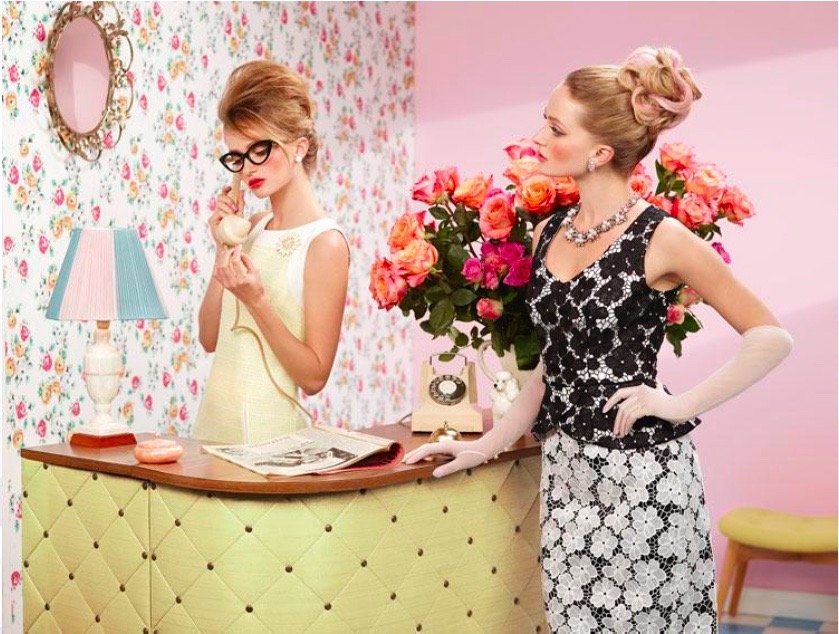Two models standing at a reception desk where one is speaking on the phone. Set in a 1950's - 1960's setting of wallpapered walls, big vase of flowers and vinyl studded and padded desk. Girls are coiffed with up styles in beehive style, one wearing black heavy plastic spectacles, and vintage clothing.
