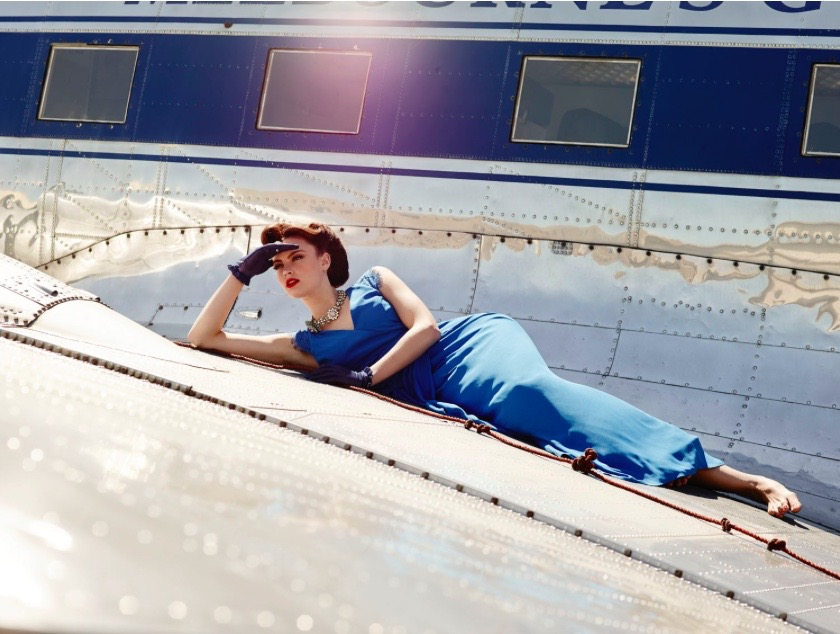 Model lying on the wing of an aircraft in blue outfit with short gloves, 1950's style with her hand to her head and looking out to the distance.