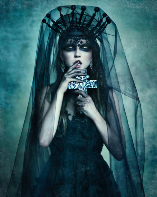 Model standing in the style of a bride, but dressed in black with a black veil, very heavy makeup and a black dress.
