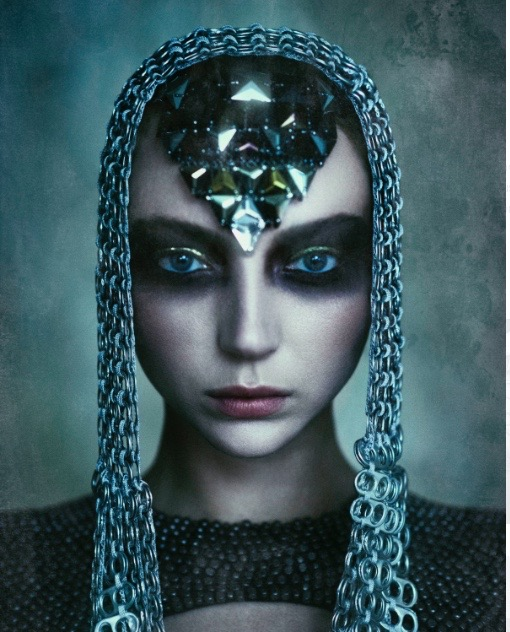 Model with mediaeval headress on with black triangular gem detail covering her forehead. Shades of black, grey, green, and extremely heavy makeup, looking straight at the camera with a grey and white blotchy wall behind her.