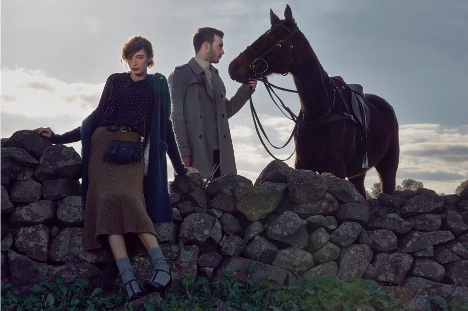 Two models, a man and a woman in an outside shoot standing on large rocks with a horse. The sky is grey in the background and it is late in the day with a feeling of cooler weather.