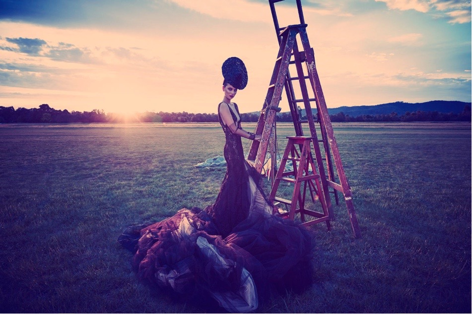 Model standing outside on a large area of open rural area with a standing ladder behind her in a long chiffon gown with a train and wearing a hat and gloves styled in a very vintage way with the sun setting behind her.