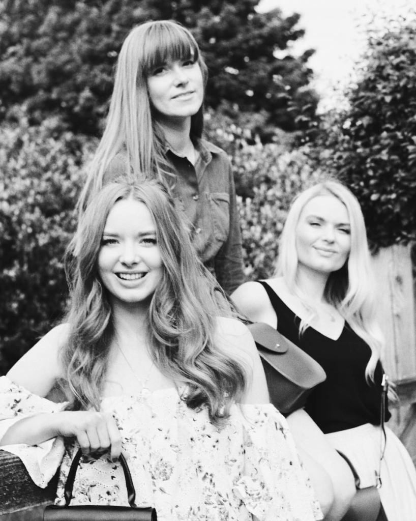 Three girls sitting together, one of whom is the British handbag designer, Charlotte Elizabeth.