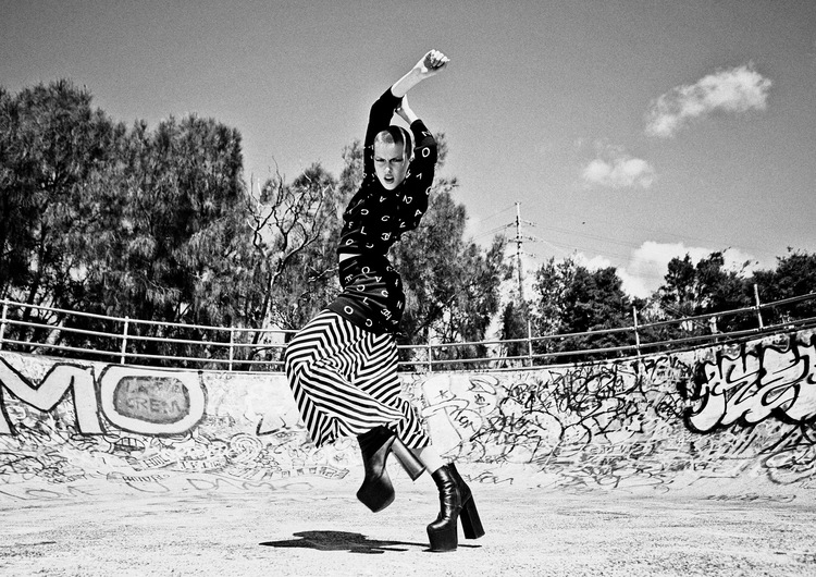 Girl in black and white photographed jumping in the centre of a skate park with hands outstretched above her head.
