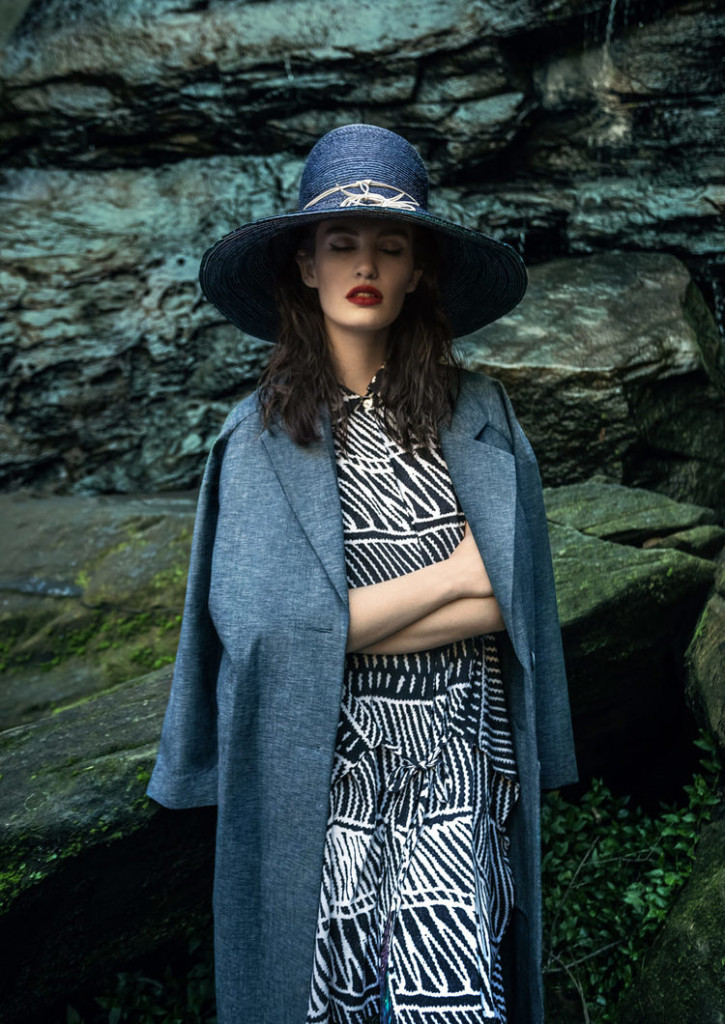 Model shot on location standing in front of rocks and cliff face at a beach setting dressed in 1950's attired, black and white dress with blue coat draped over her shoulders and matching hat with white trim.