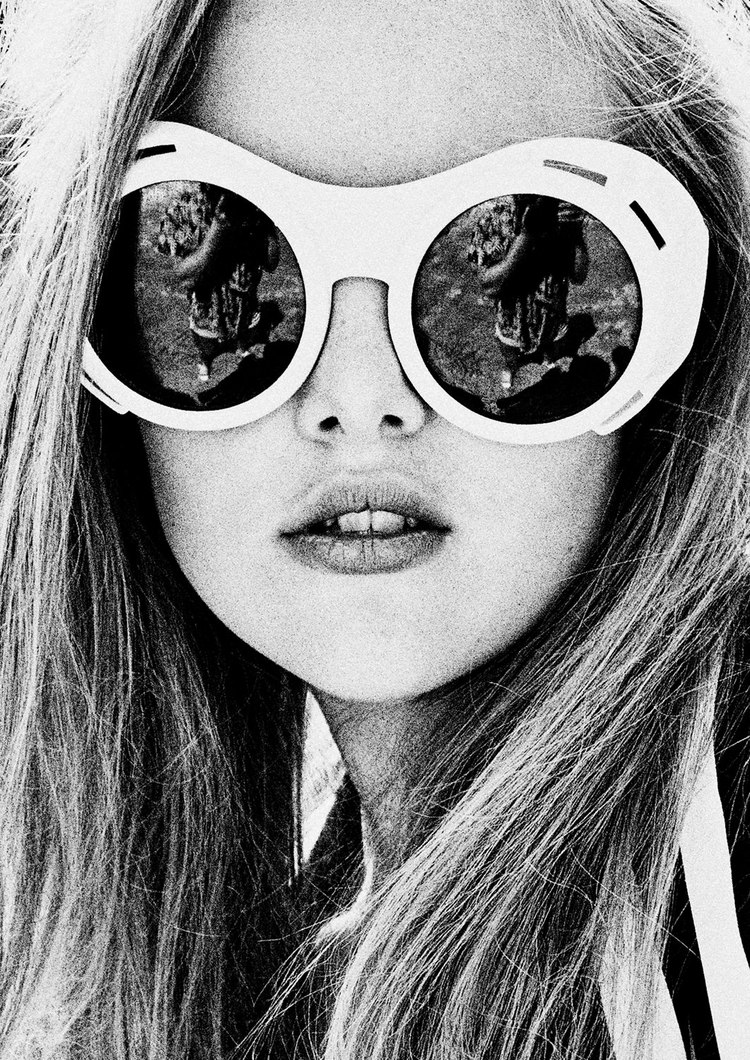 Picture of a girl in black and white with large round sunglasses and long brown hair.