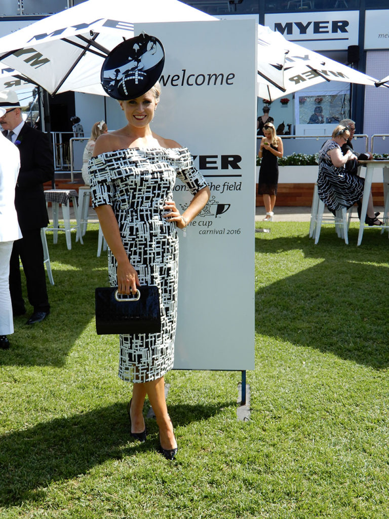 Alice Bright standing in a black and white dress, black clutch, black shoes, black hat by Allport Millinery.