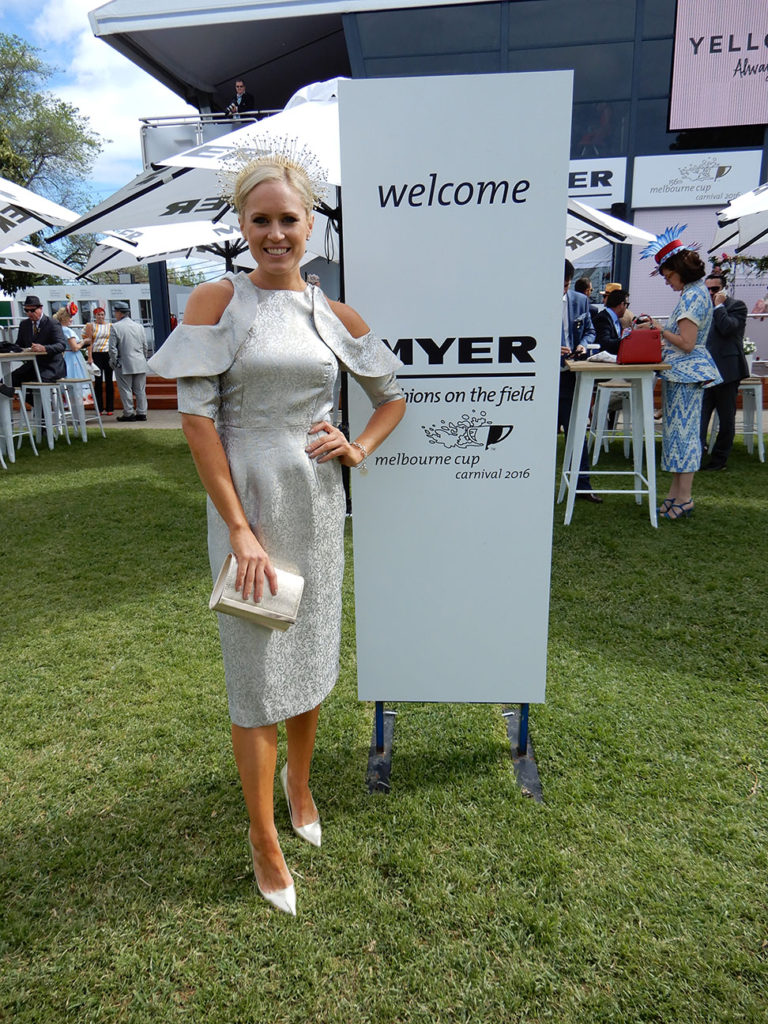 Alice Bright standing in front of the Myer, Fashions on the Field in a silver dress.