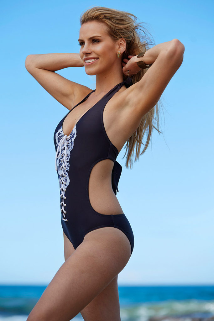 Girl standing in a modelling shoot wearing a black and white one piece costume with her hands up holding her hair away from her face.