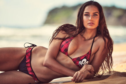 Dark haired girl lying on the beach resting on her elbow looking at the camera wearing a red checked bikini with a picture of Felix the Cat on her left breast in a modelling shoot for a swimwear label.