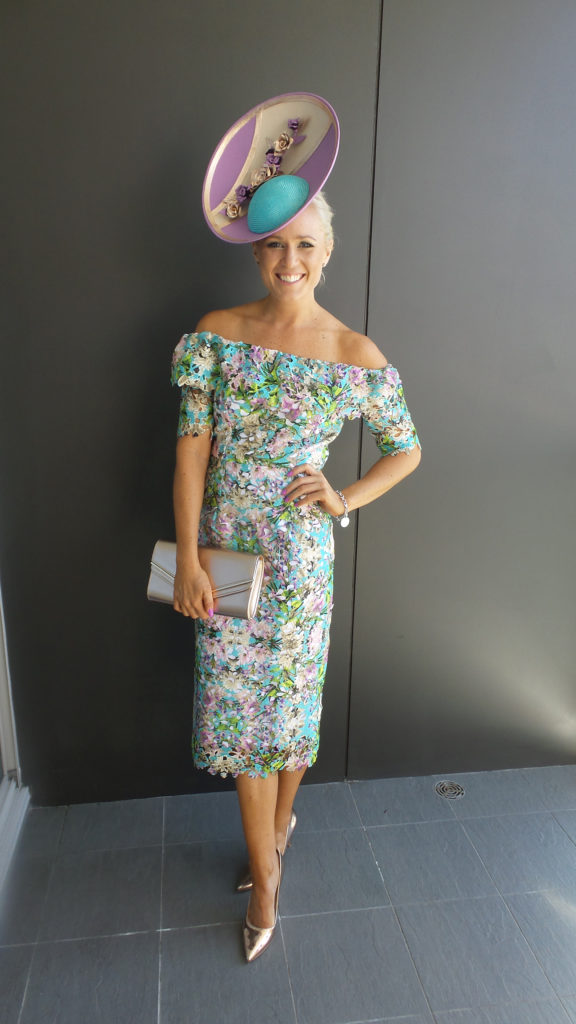 Alice Bright standing in a pastel coloured dress, completely hand made by her, matching hat by Allport Millinery.