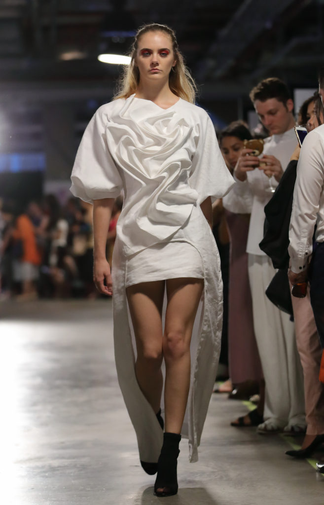 Model on the runway wearing a white ruffled design by Ruth Read from Raffles College of Design Graduate Runway 2016.