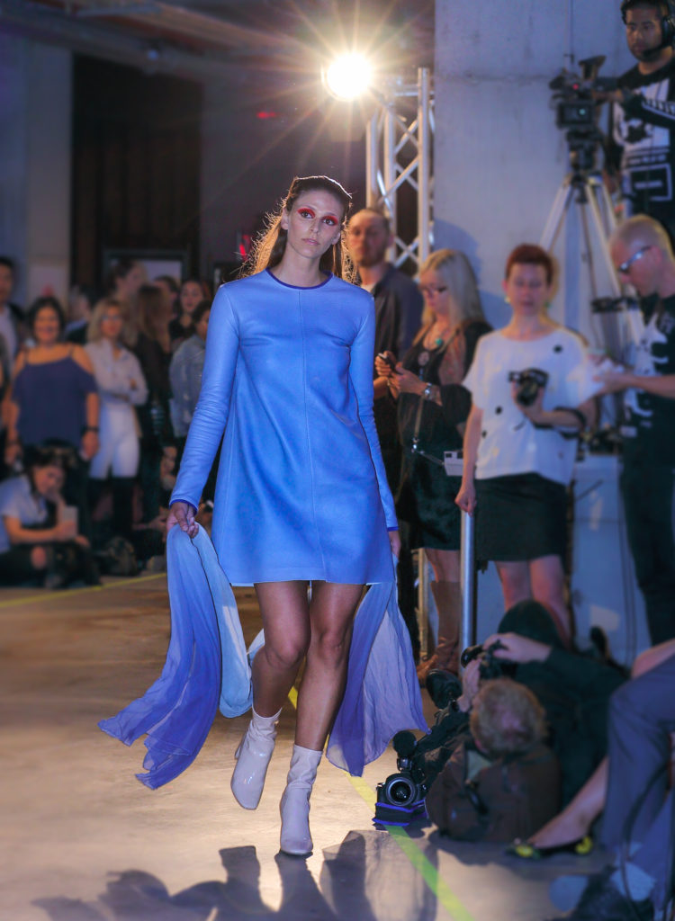 Model on the runway wearing a cornflower blue leather dress by emerging designer Alyce Chen.