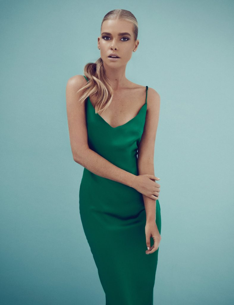 Model standing in front of a pale blue wall in an emerald green slinky dress by Dida.