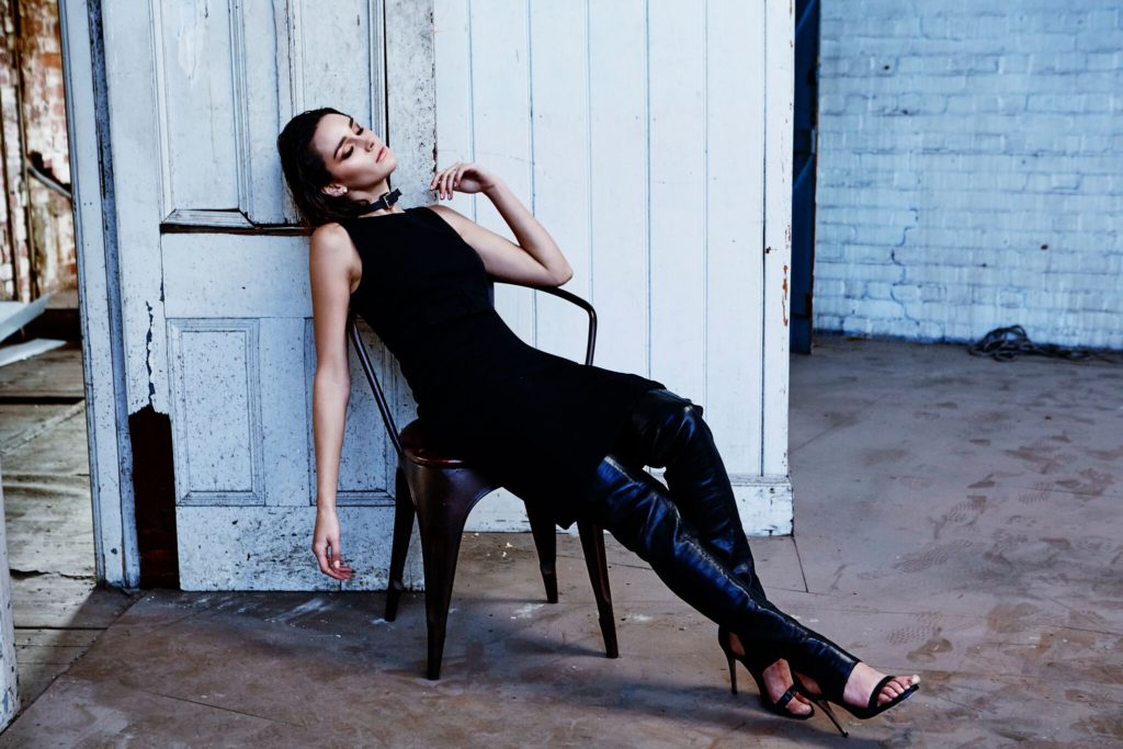 Girl sitting on a chair slouched back in a modelling shoot with black top, black leather pants and high black stilettos.