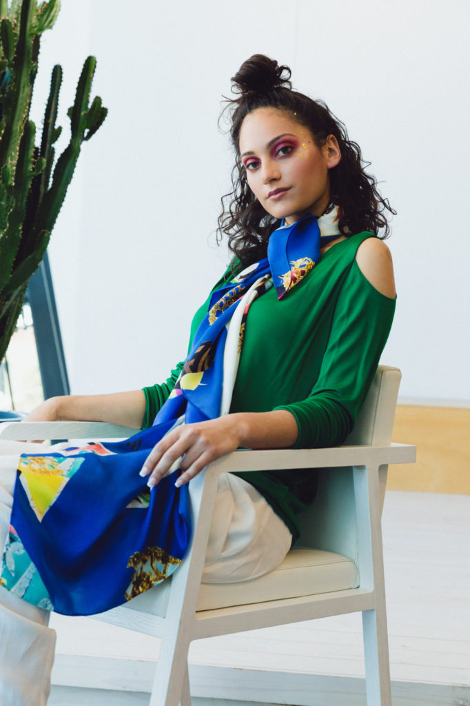Model sitting for a photographic shoot for designer scarf label Valentina Avramides in an emerald green top with open shoulders and white trouser.