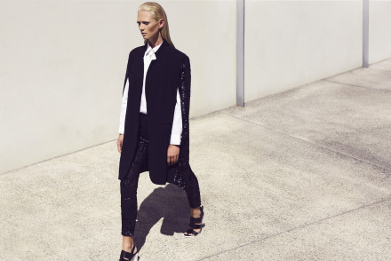 Model walking and being photographed in the full sunlight against a white wall wearing a black pant and black winter jacket with white shirt and heels